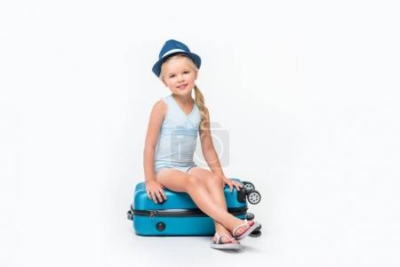 child in swimsuit sitting on suitcase