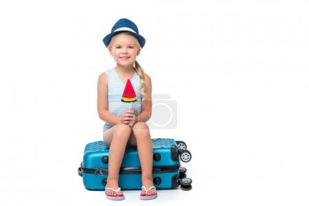 Happy child sitting on suitcase