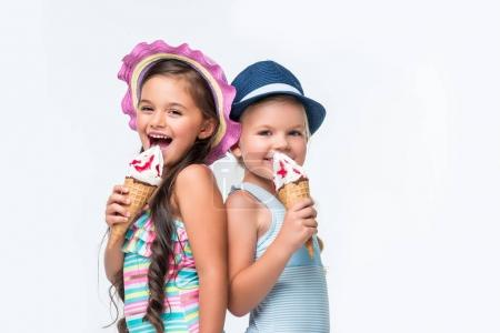 Photo for Beautiful happy little girls in swimwear eating ice cream isolated on white - Royalty Free Image