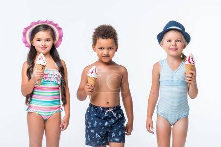 Photo pour Adorables enfants multiethniques en maillots de bain mangeant de la crème glacée et souriant à la caméra isolée sur blanc - image libre de droit
