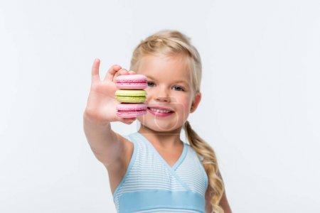 Photo pour Vue rapprochée d'adorable petite fille souriante tenant des macarons isolés sur blanc - image libre de droit