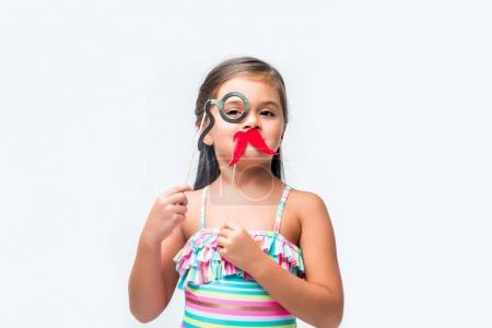 Photo for Cute little girl holding false moustache and monocle on party sticks isolated on white - Royalty Free Image