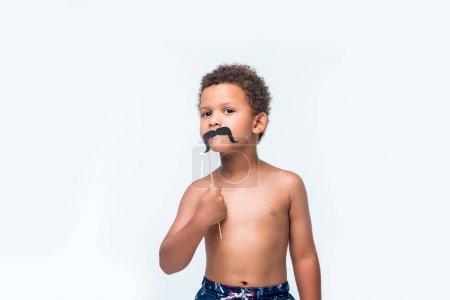 Photo pour Mignon afro-américain garçon tenant fausse moustache et regardant caméra isolé sur blanc - image libre de droit