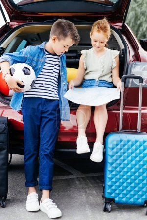 Brother and sister in trunk of car
