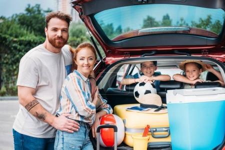 Photo pour Belle jeune famille emballant des bagages dans le coffre de voiture - image libre de droit