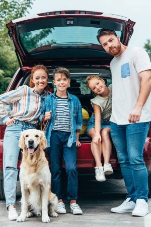 family with dog standing next to car