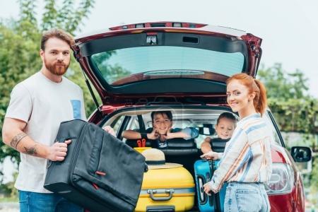 Photo pour Jeunes parents emballant des bagages dans le coffre de la voiture avec des enfants regardant depuis les sièges arrière - image libre de droit