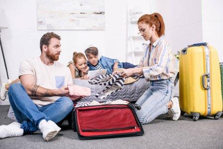 Photo pour Heureux bagages d'emballage de famille pour le voyage dans la chambre - image libre de droit