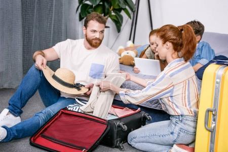 Photo pour Heureux famille emballage bagages pour le voyage ensemble dans la chambre - image libre de droit