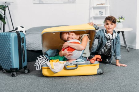 Photo for Adorable kids packing clothes for trip while girl sitting in suitcase - Royalty Free Image