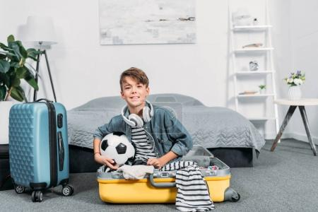 boy sitting in suitcase for trip
