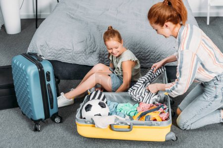 mother and daughter packing clothes for trip