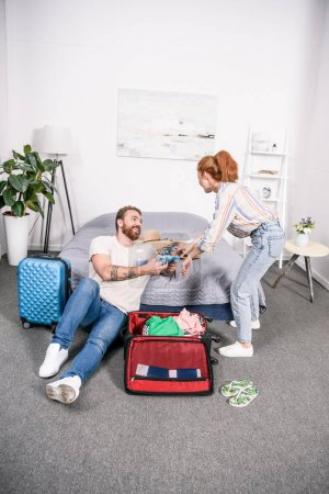 couple packing clothes for trip