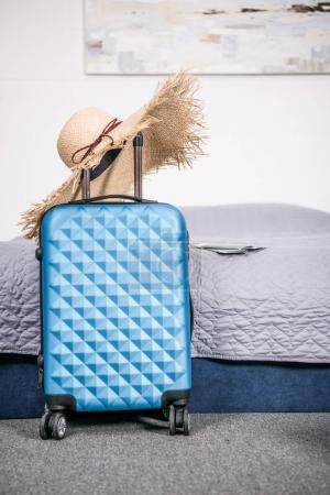 Photo for Suitcase for trip with straw hat in bedroom - Royalty Free Image