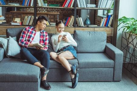 students with smartphone and book