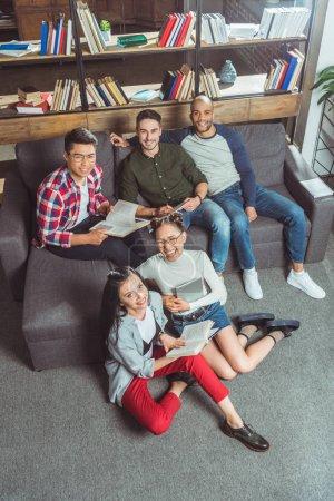 Photo pour Vue grand angle des étudiants multiethniques heureux étudiant ensemble et souriant à la caméra - image libre de droit