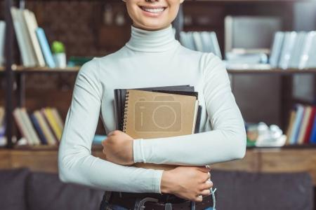 Photo for Cropped shot of smiling asian student holding books in library - Royalty Free Image