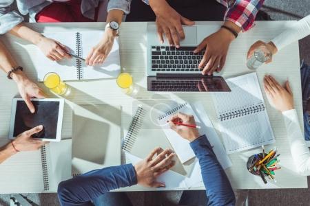 Photo pour Vue de dessus des étudiants avec des appareils numériques et ordinateurs portables étudient ensemble - image libre de droit