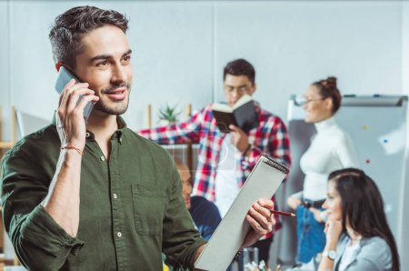 man with clipboard talking on smartphone