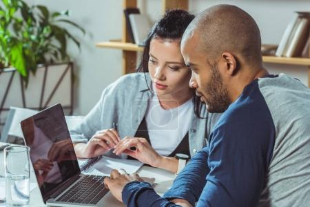 multiethnic couple using laptop