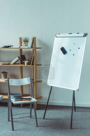 whiteboard and books on chair