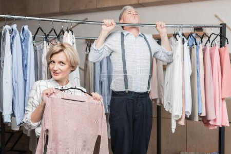 Photo for Woman posing with shirt while man pulling up on a clothes rack in a store - Royalty Free Image