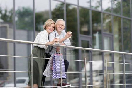Photo pour Femme et mari buvant du café après avoir fait du shopping avec des sacs en papier - image libre de droit