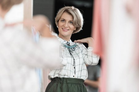Photo for Woman trying on a necklace at the store in front of mirror - Royalty Free Image