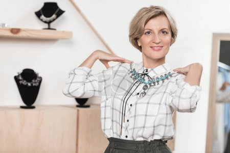 Photo for Woman trying on a necklace at the store - Royalty Free Image