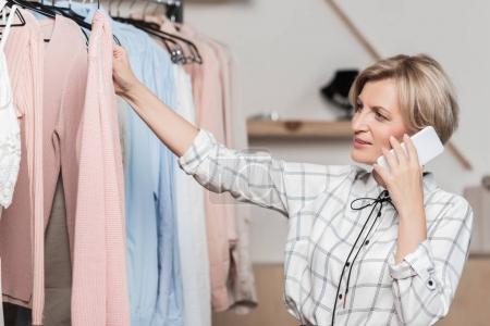 woman talking by smartphone in shop