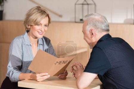 Photo pour Femme et homme, choisir des aliments du menu au café - image libre de droit