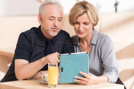 Photo pour Couple regardant quelque chose à tablette assis au café - image libre de droit