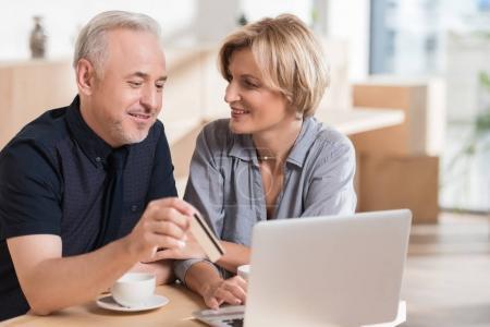 Photo pour Couple affectueux qui veulent acheter quelque chose en ligne et payer par carte de crédit - image libre de droit