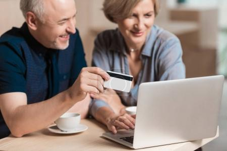 Photo pour Charmant couple voulant acheter quelque chose en ligne et payer par carte de crédit - image libre de droit