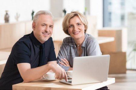 Couple sitting at table with laptop