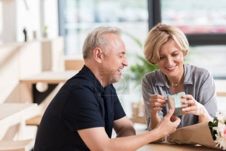 Photo for Man presenting a gift box and flowers to woman - Royalty Free Image