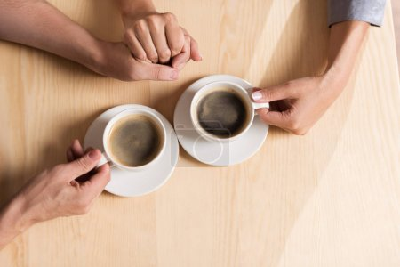 Couple holding by hands and drinking coffee
