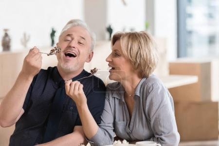 Photo for Affectionate Couple laughing and eating sweets at cafe - Royalty Free Image