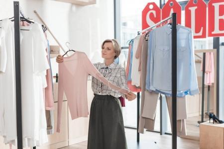 woman looking at pink shirt