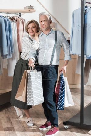 Foto de Mujer y hombre de pie con bolsas entre los estantes con ropa en boutique - Imagen libre de derechos