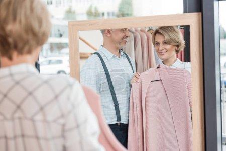 woman choosing pink shirt