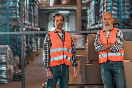 Photo for Confident warehouse workers in vests looking at camera in storehouse - Royalty Free Image