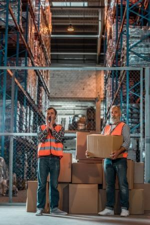 Foto de Vista de la longitud total de dos hombres con chalecos con cajas en almacén - Imagen libre de derechos