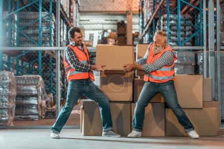 Photo for Two male workers in vests holding box in warehouse - Royalty Free Image