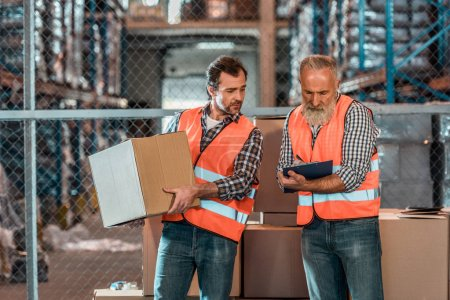 Photo for Bearded man taking notes on clipboard while colleague holding box in warehouse - Royalty Free Image
