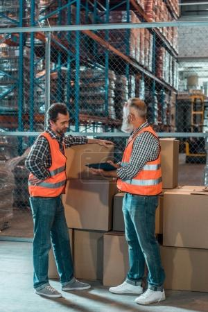 Photo for Two men in vests writing on clipboard while working with boxes in warehouse - Royalty Free Image