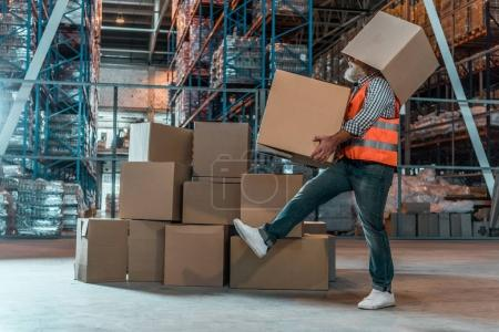 Photo for Side view of bearded warehouse worker with boxes walking in storehouse - Royalty Free Image