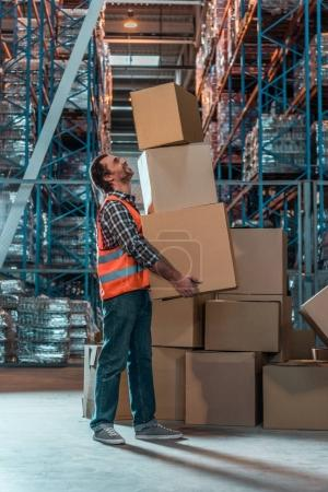 Photo for Side view of male warehouse worker holding stacked boxes - Royalty Free Image