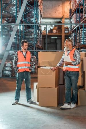 Photo for Warehouse workers with digital tablet standing near boxes and looking at each other - Royalty Free Image