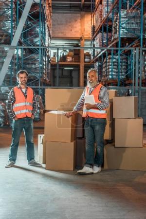 Photo pour Deux magasiniers mâle avec tablette numérique, souriant à la caméra - image libre de droit